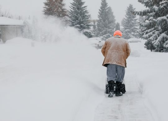 A man pushes a snow blower down a residential street during a winter blizzard.